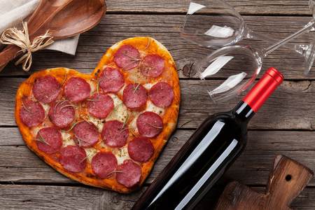 Heart shaped pizza with pepperoni and mozzarella and red wine bottle. Valentines day greeting card.