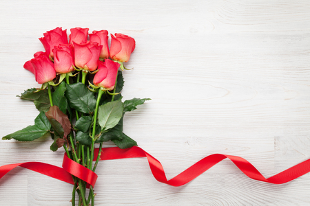 Valentines day greeting card with red roses on wooden background. Top view with space for your greeting