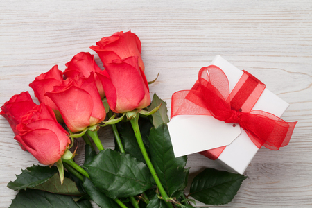 Valentines day gift box and red roses on wooden background. Top view with space for your greetings