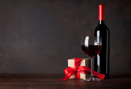 Valentines day greeting card with red wine and gift box on wooden table. With chalkboard for your greetings