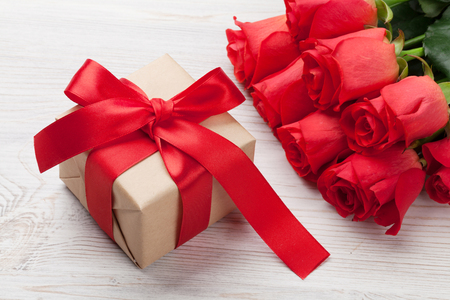 Valentines day gift box and red roses on wooden background