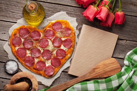 Heart shaped pizza with pepperoni and mozzarella and red rose flowers bouquet. Valentines day greeting card. With space for your greetings Standard-Bild