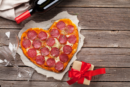 Heart shaped pizza with pepperoni and mozzarella and red wine bottle. Valentines day greeting card. Top view with space for your greetings Standard-Bild
