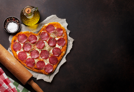 Heart shaped pizza with pepperoni and mozzarella. Valentines day greeting card. Top view with space for your greetings