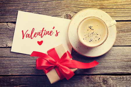 Valentines day greeting card. Red coffee cup and gift box on wooden table. Top view with copy space