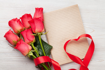 Valentines day greeting card with red roses and heart shaped ribbon on wooden background. Top view with space for your greeting Standard-Bild