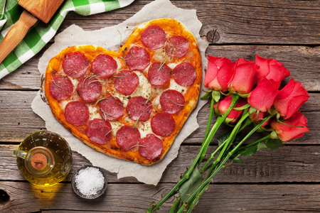 Heart shaped pizza with pepperoni and mozzarella and red rose flowers bouquet. Valentines day greeting card. Foto de archivo
