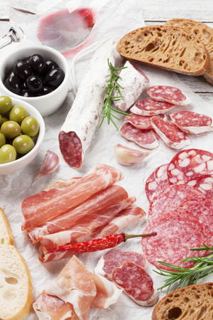 Salami, sliced ham, sausage, prosciutto, bacon, toasts, olives. Meat antipasto platter and red wine on wooden table Archivio Fotografico