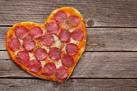 Heart shaped pizza with pepperoni and mozzarella. Valentines day greeting card. Top view