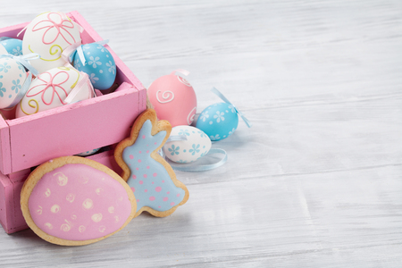 Easter gingerbread cookies and eggs on wooden table. Colorful rabbits. With space for your greetings