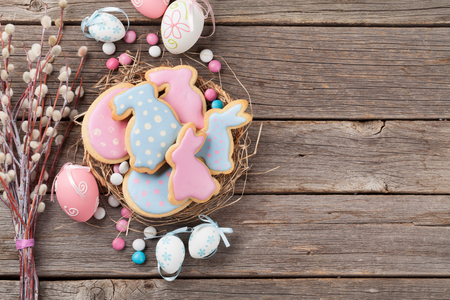 Easter gingerbread cookies and eggs on wooden table. Colorful rabbits. Top view with space for your greetings