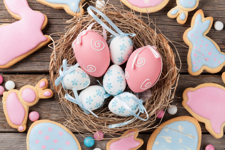 Easter gingerbread cookies and eggs on wooden table. Colorful rabbits. Top view Stock Photo