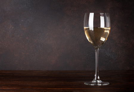 White wine glass in front of blackboard wall. With copy space for your text
