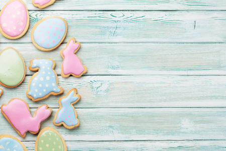 Easter gingerbread cookies on wooden table. Eggs and rabbits. Top view with space for your greetings