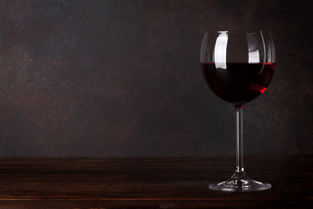 Red wine glass in front of blackboard wall. With copy space for your text Foto de archivo