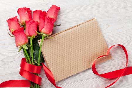 Valentines day greeting card with red roses and heart shaped ribbon on wooden background. Top view with space for your greeting Stock Photo
