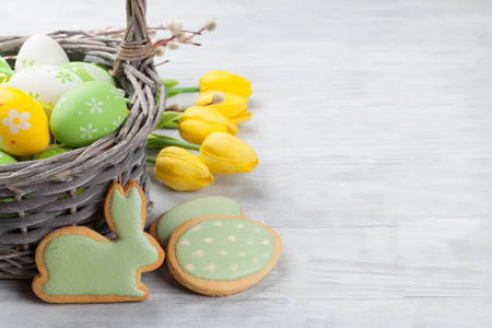 Easter eggs, gingerbread cookies and tulip flowers on wooden table. Greeting card. With space for your greetings