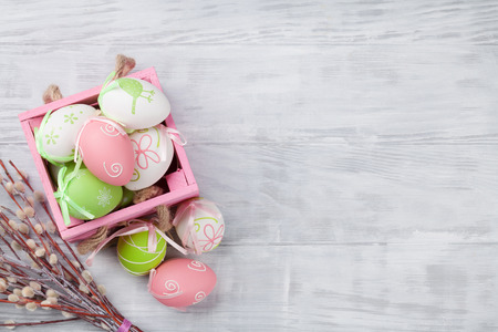 Easter eggs in box on wooden table. Top view with space for your greetings
