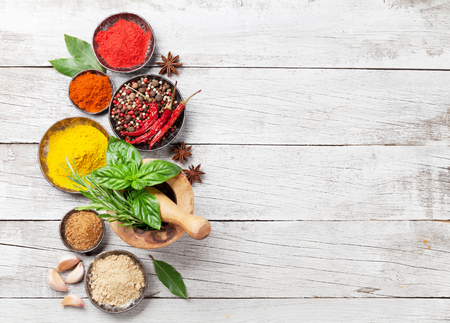 Various spices and herbs on wooden table. Top view with space for your text Stock Photo