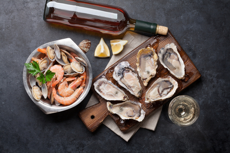 Fresh seafood and white wine on stone table. Oysters, prawns and scallops. Top view Stockfoto
