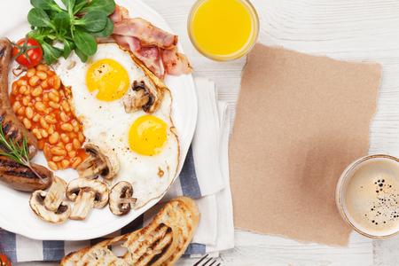 Englisches Frühstück. Spiegeleier, Würste, Speck, Bohnen, Toast, Tomaten, Orangensaft und Kaffeetasse auf Holztisch. Standard-Bild - 94908844