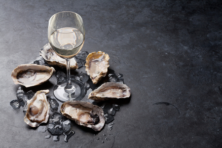 Opened oysters, ice and lemon and white wine on stone table. With copy space