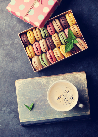 Colorful macaroons and coffee on stone table. Sweet macarons in gift box. Top view. Retro toned