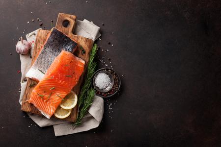 石のテーブルの上で調理スパイスと生のサーモンの魚のフィレ。テキスト用のスペースを含むトップ ビュー