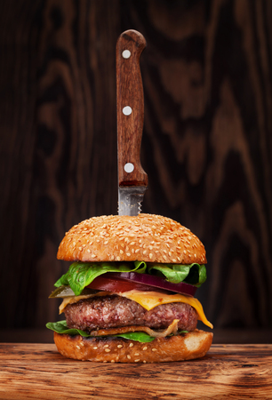 Tasty grilled home made burger with beef, tomato, cheese, cucumber and lettuce Stock Photo