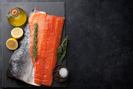 Raw salmon fish fillet with spices cooking on stone table. Top view with space for your text