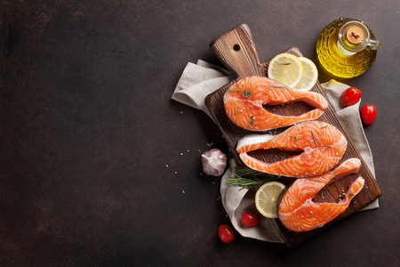 Raw salmon fish fillet with spices cooking on cutting board. Top view with space for your text