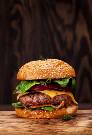 Tasty grilled home made burger with beef, tomato, cheese, cucumber and lettuce. With copy space Stockfoto