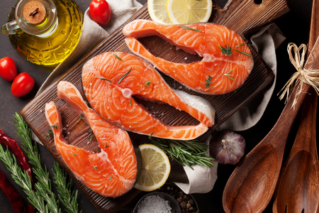 Raw salmon fish fillet with spices cooking on cutting board. Top view Stockfoto