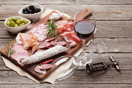 Salami, sliced ham, sausage, prosciutto, bacon, toasts, olives. Meat antipasto platter and red wine on wooden table Stock Photo