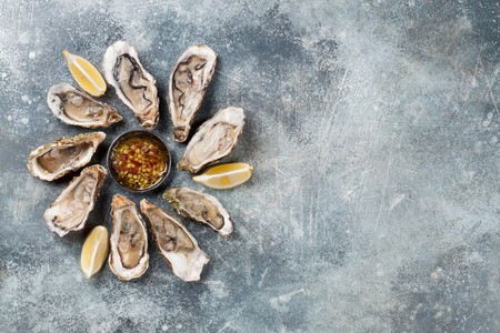 Fresh oysters on stone table. Top view with space for your text