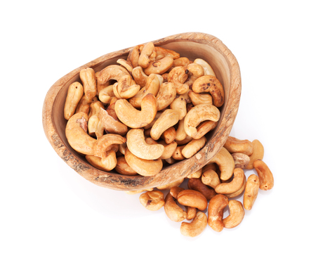 Cashew nuts in bowl. Isolated on white background. Top view