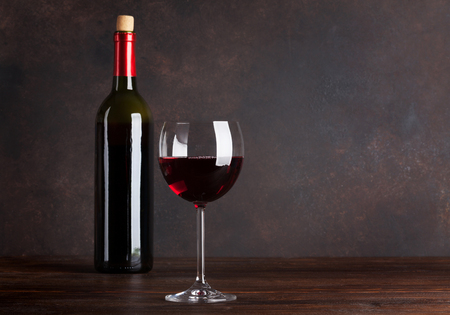 Red wine bottle and glass in front of blackboard wall. With copy space for your text Stockfoto
