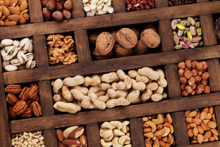 Various nuts selection: peanuts, hazelnuts, chestnuts, walnuts, pistachio and pecans in a wooden box. Top view