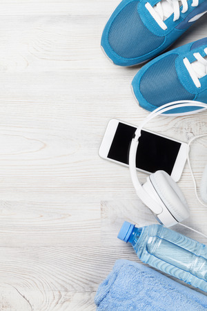 Fitness concept background with sneakers, smartphone, water bottle and headphones on wooden backdrop. Top view with space for your text 스톡 콘텐츠