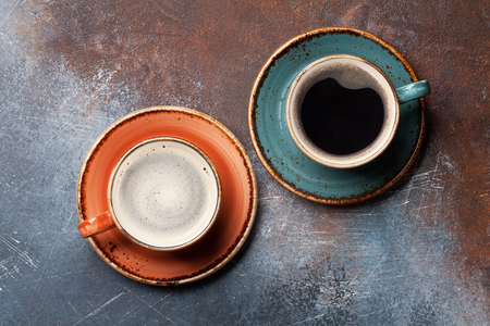 Retro colorful coffee cups on rust background. Top view