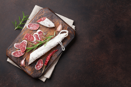 Sliced salami on cutting board. Top view with space for your text