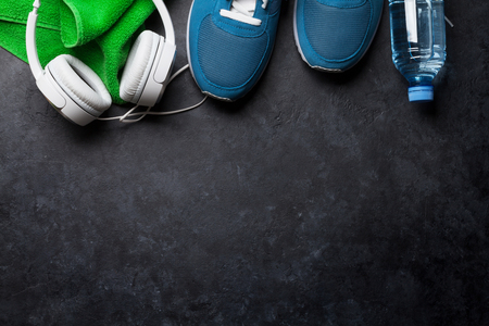 Fitness concept background with sneakers, water bottle, towel and headphones. Top view with space for your text