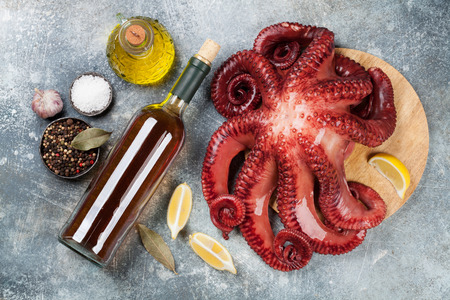 Raw octopus cooking with spices and white wine on stone table. Seafood. Top view Standard-Bild