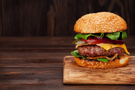 Tasty grilled home made burger with beef, tomato, cheese, cucumber and lettuce. With copy space Foto de archivo