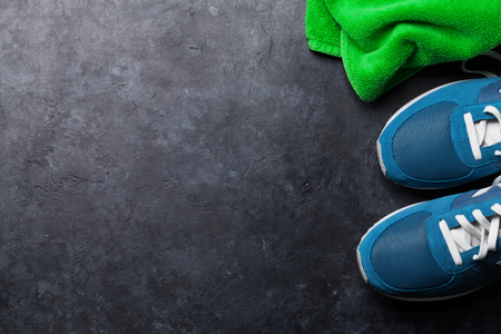 Fitness concept background with sneakers and towel. Top view with space for your text