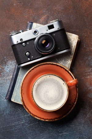 Coffee cup and retro camera over book. Top view