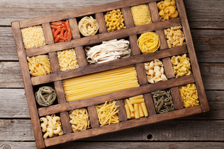 Various pasta in wooden box. Cooking concept. Top view