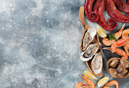 Seafood. Octopus, oysters, lobster, shrimps, clams cooking. Top view on stone table with space for your text Standard-Bild
