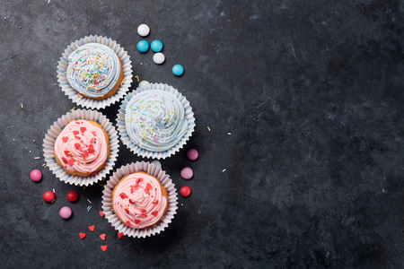Sweet cupcakes with colorful decor and candies. Top view with space for your greetings Standard-Bild
