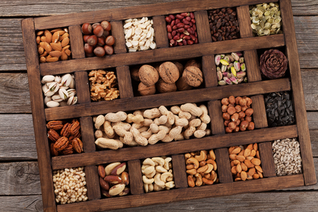 Various nuts selection: peanuts, hazelnuts, chestnuts, walnuts, pistachio and pecans in wooden box. Top view